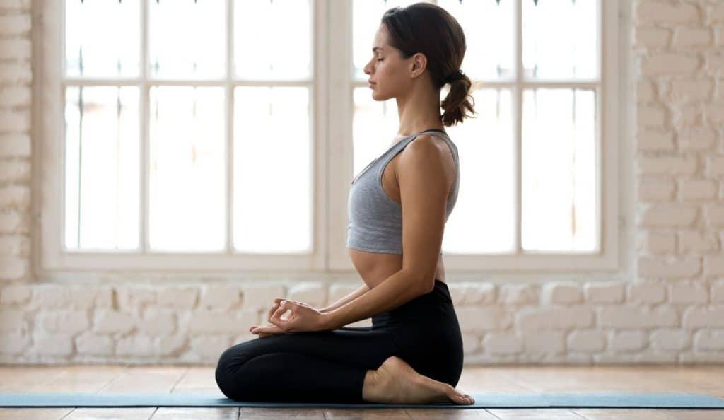 femme pratiquant le yoga à genou