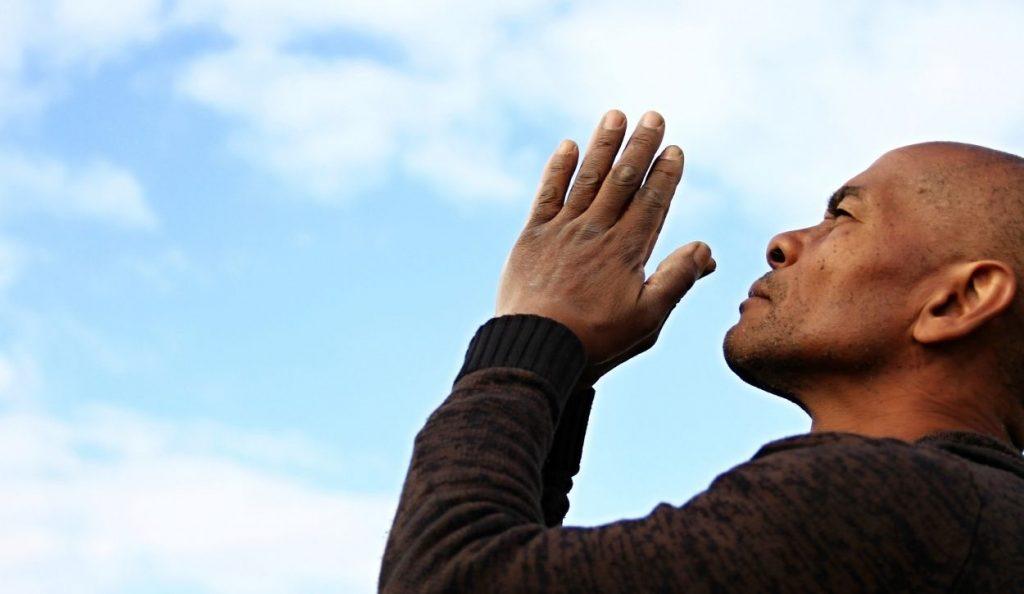 homme priant regardant vers le ciel
