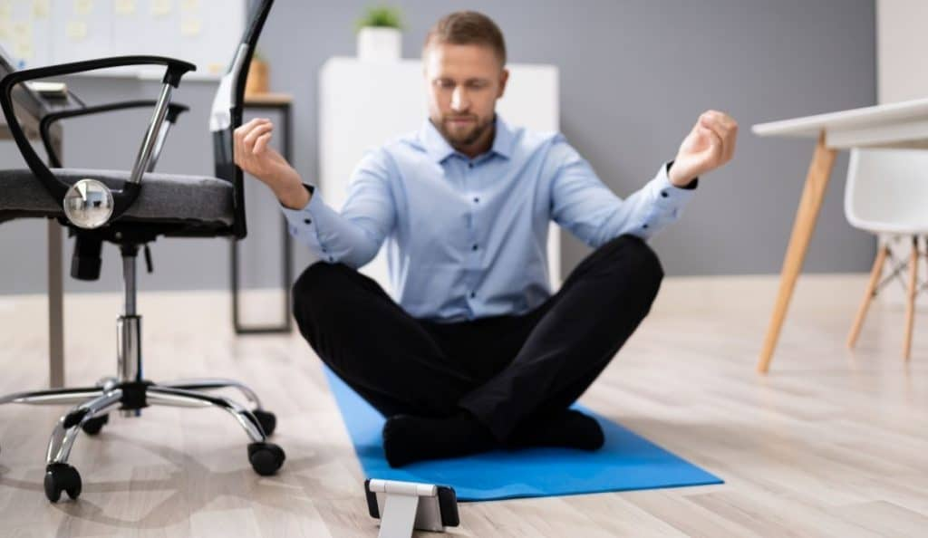 man meditating indoor using mobile